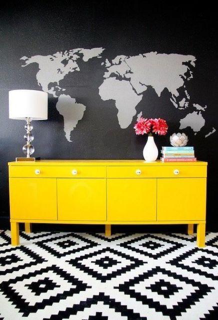 La peinture murale noire et grise de la carte du monde semble contrastée avec un buffet jaune fluo
