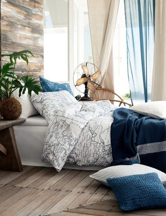 décor de chambre en bord de mer avec literie carte pour rêver de voyager avant de s'endormir
