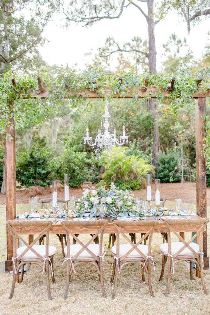 Table de mariage en plein air champêtre avec verdure suspendue